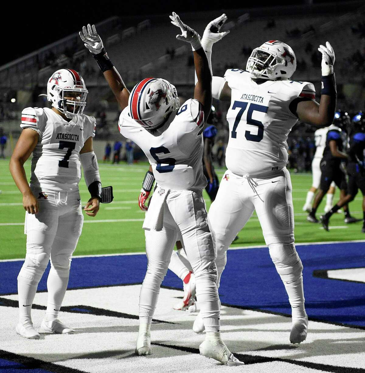 Atascocita running back Tyras Winfield (6) celebrates his touchdown with Kameron Dewberry (75) and Gavin Session (7) during the first half of a high school football game against CE King, Friday, Nov. 13, 2020, in Houston.