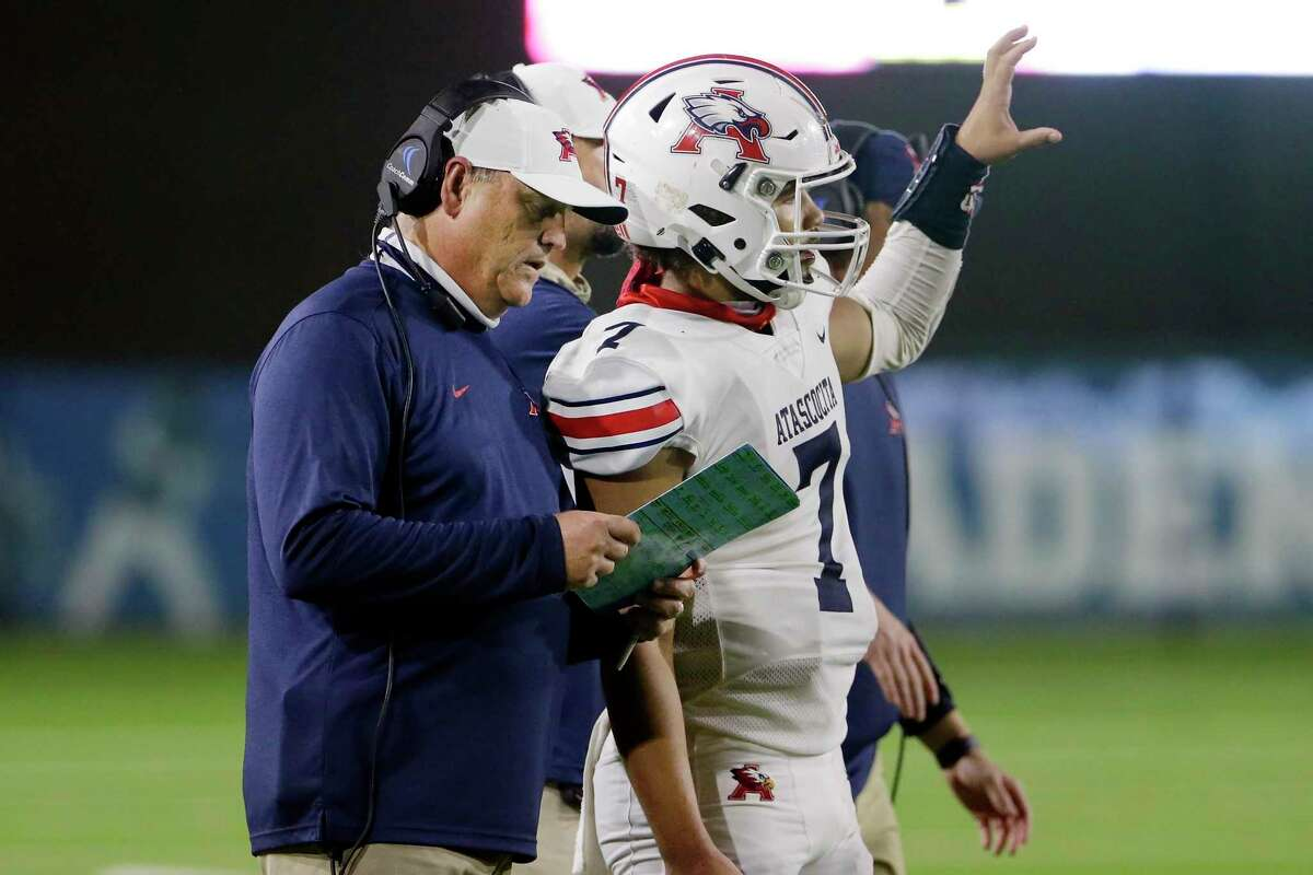 Atascocita head coach Craig Stump talks with quarterback Gavin Session during a time out during the first half of their Class 6A, Division 1 Bi-District high school football playoff game against Dobie at Veterans Memorial Stadium Friday, Dec. 11, 2020 in Pasadena, TX.