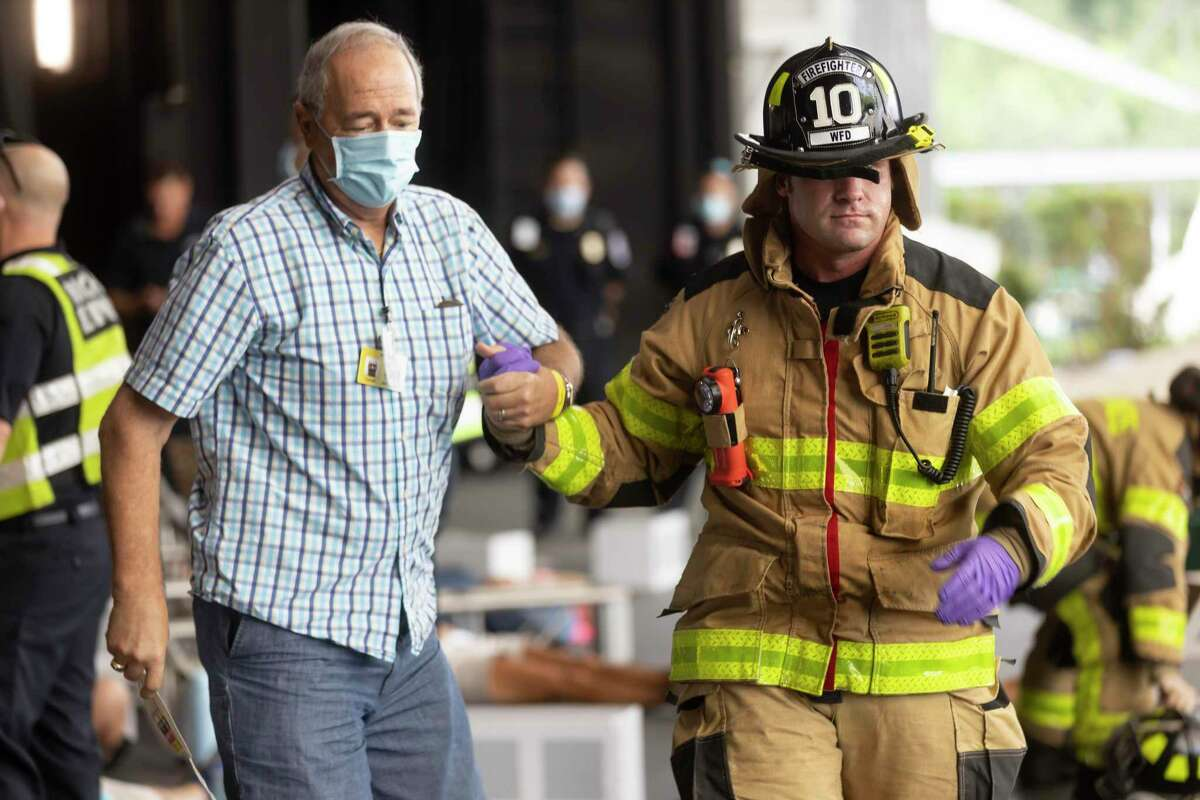 Firefighter Berryman, right, assists Darrell Boch during a four-hour-long disaster drill hosted by the Montgomery County Hospital District and Montgomery County Office of Homeland Security and Emergency Management.