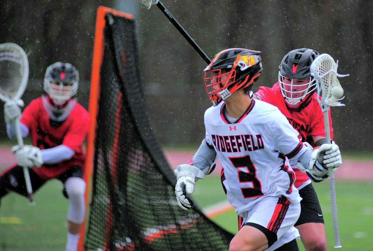 Ridgefield's Ryan Colsey (3) comes from behind the goal with the ball as New Canaan's Braden Sweeney (91) defends during boys lacrosse action in Ridgefield, Conn., on Thursday April 15, 2021.