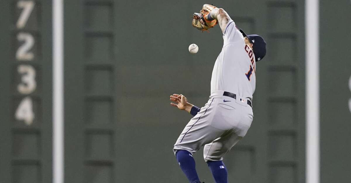 Houston Astros shortstop Carlos Correa drops a pop fly by Boston Red Sox's Rafael Devers who was ruled out due to the infield fly rule in the sixth inning of a baseball game at Fenway Park, Thursday, June 10, 2021, in Boston. (AP Photo/Elise Amendola)