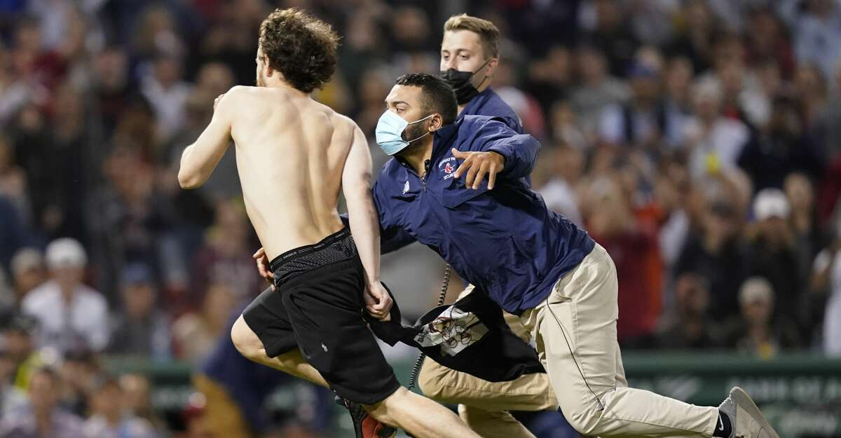 Fenway Park security run after a fan after he ran onto the playing field in the sixth inning of a baseball game between the Boston Red Sox and the Houston Astros at Fenway Park, Thursday, June 10, 2021, in Boston. (AP Photo/Elise Amendola)