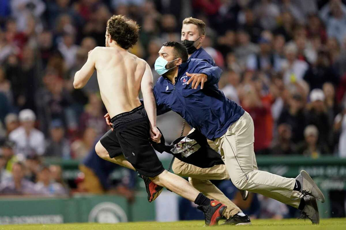 Fenway Park security runs after a fan after running onto the playing field in the sixth inning of a baseball game between the Boston Red Sox and the Houston Astros at Fenway Park on Thursday, June 10, 2021, in Boston.  (AP Photo / Elise Amendola)
