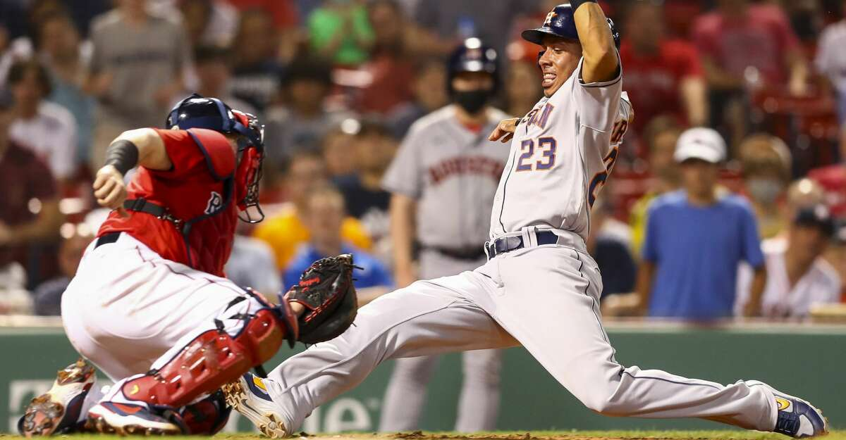 Michael Brantley #23 of the Houston Astros sides safely into home plate past the tag of Christian Vazquez #7 of the Boston Red Sox in the seventh inning of a game at Fenway Park on June 9, 2021 in Boston, Massachusetts. (Photo by Adam Glanzman/Getty Images)