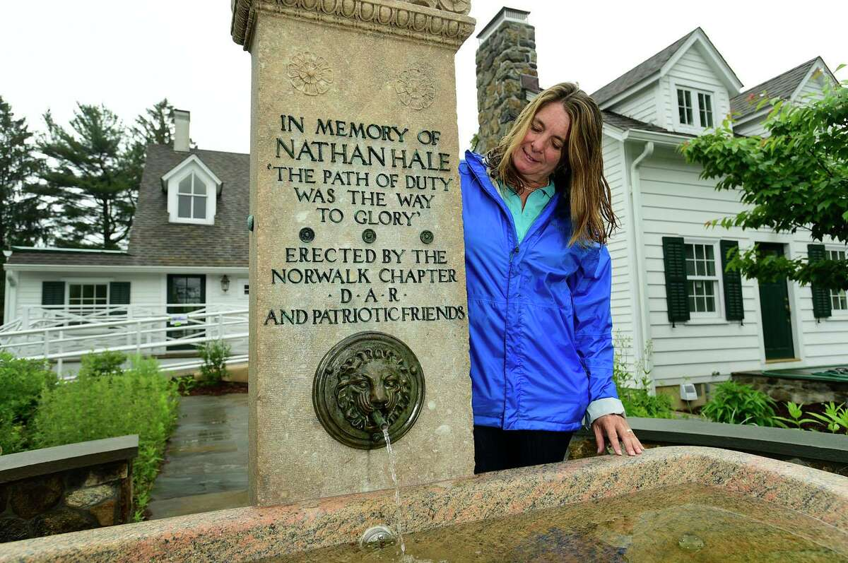 Local historian and DAR member Lisa Grant and the restored Nathan Hale memorial fountain Thursday, June 3, 2021, at Fodor Farm in Norwalk, Conn. Lisa Grant spearheaded the refurbishment of the Nathan Hale fountain which was originally dedicated in 1901 and rededicated June 6.