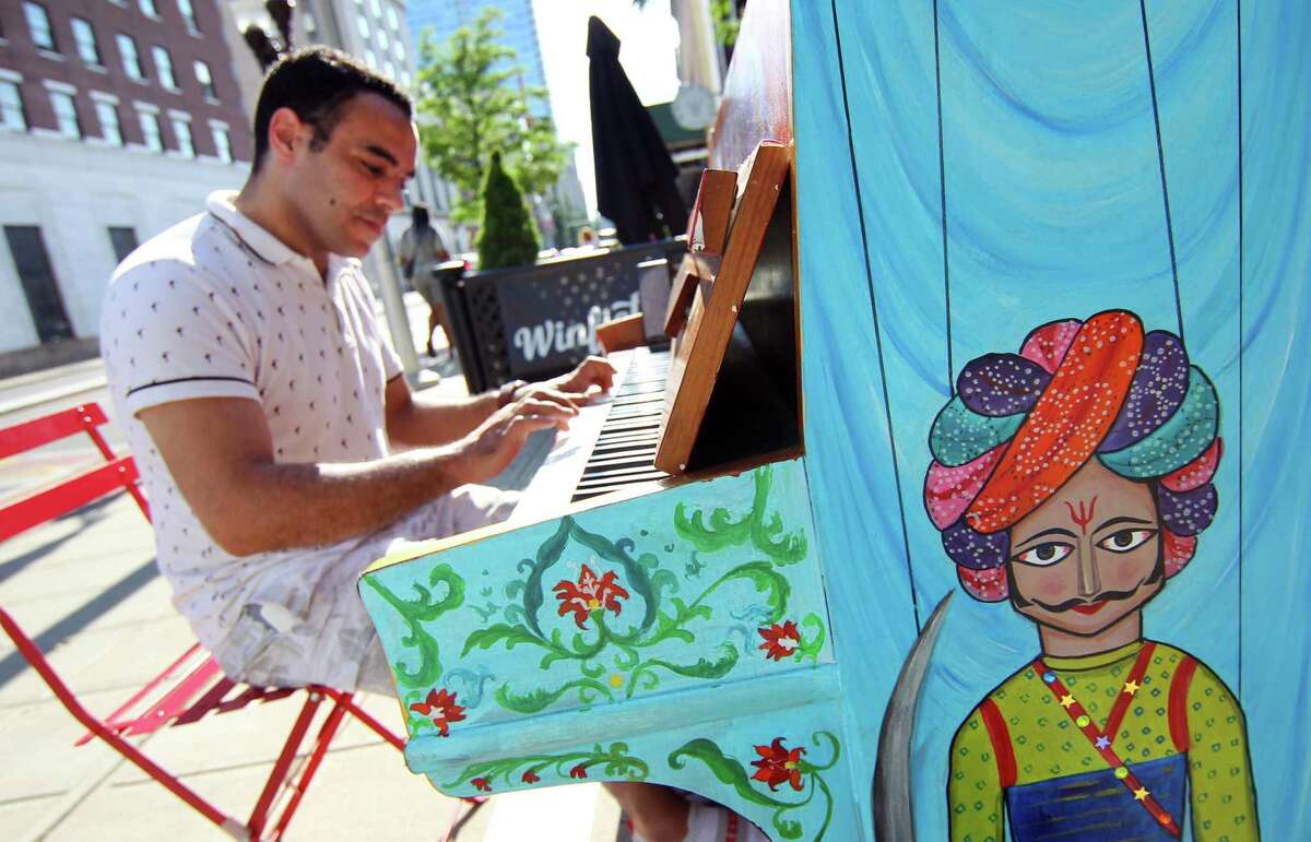Above, Abdelilah Et Taqy, of Stamford, plays one of the 25 pianos spread out throughout downtown Stamford during the start of The Piano Project in Stamford on Wednesday. The Piano Project in Stamford Downtown is the 10th exhibit of its kind and the 28th annual sculpture exhibit produced by the Stamford Downtown Special Service District. They have installed 25 donated pianos, that have been transformed into originally designed and painted art pieces. The pianos are on display for playing by thousands of area residents and visitors from June through September.