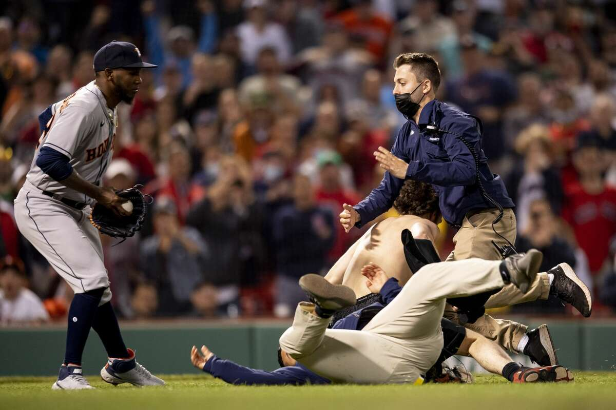 BOSTON, MA - JUNE 10: A fan is tackled as he runs onto the field during the sixth inning of a game between the Boston Red Sox and the Houston Astros on June 10, 2021 at Fenway Park in Boston, Massachusetts. (Photo by Billie Weiss/Boston Red Sox/Getty Images)