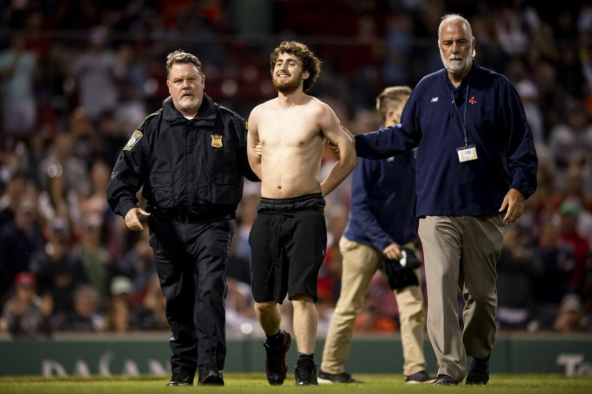 BOSTON, MA - JUNE 10: A fan is escorted after running onto the field in the sixth inning of a game between the Boston Red Sox and the Houston Astros on June 10, 2021 at Fenway Park in Boston, Massachusetts.  (Photo by Billie Weiss / Boston Red Sox / Getty Images)