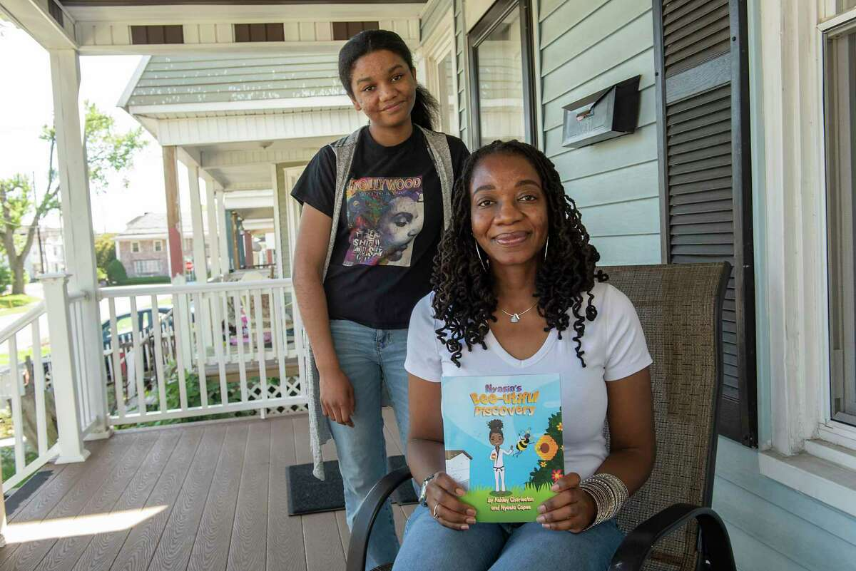 Ashley Charleston holds her book while sitting on her porch next to her niece Nyasia Copes on Thursday, June 10, 2021 in Schenectady, N.Y. Charleston is a self-published Schenectady-based children's book author who wrote a story Nyasia's Bee-utiful Discovery, about her niece, Nyasia. (Lori Van Buren/Times Union)