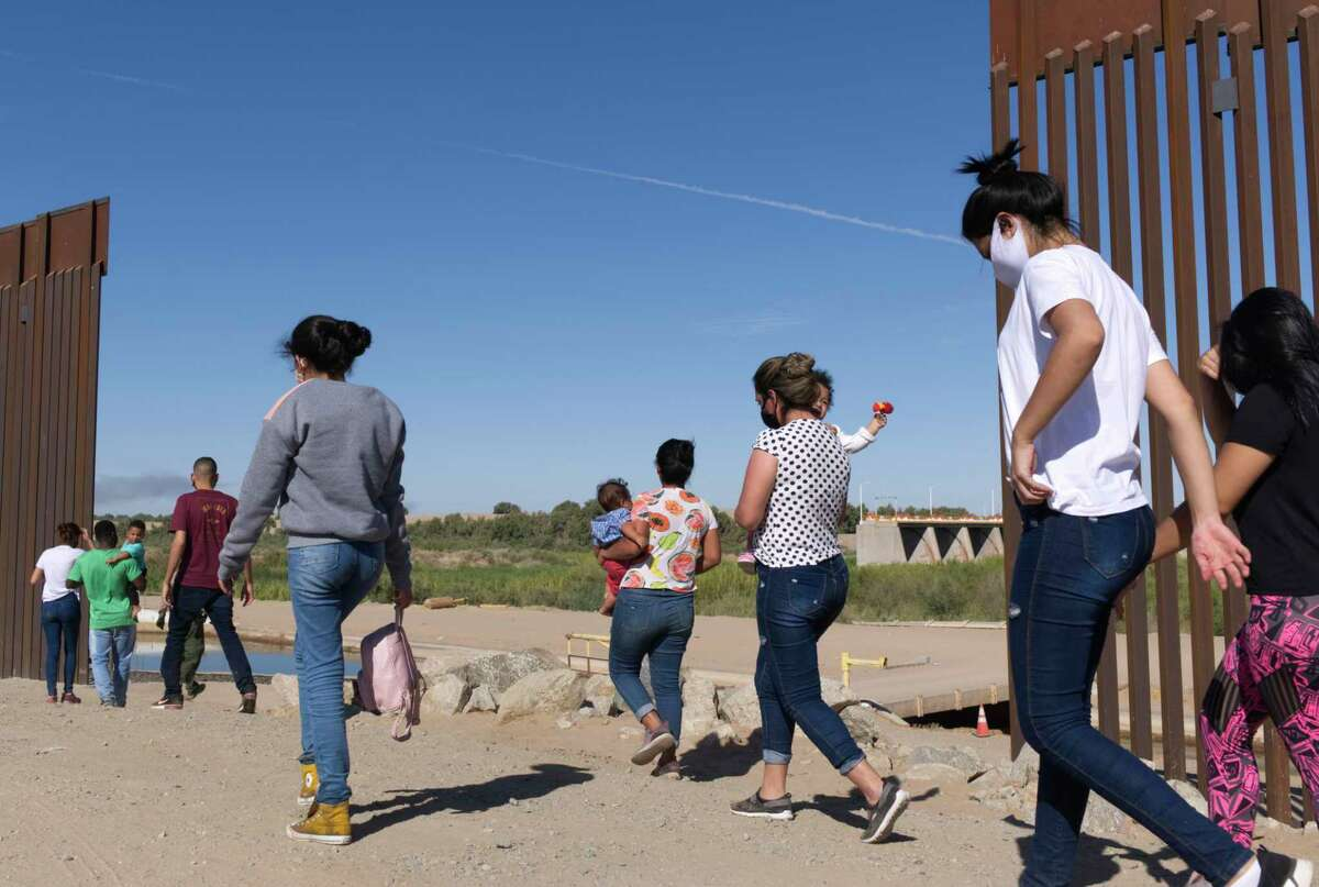 """In this Tuesday, June 8, 2021, photo, a group of Brazilian migrants make their way around a gap in the U.S.-Mexico border in Yuma, Ariz., seeking asylum in the United States after crossing over from Mexico. The Biden administration says it has identified more than 3,900 children separated from their parents at the U.S.-Mexico border under former President Donald Trump's """"zero-tolerance"""" policy on illegal crossings. The Border Patrol's Yuma sector recorded the highest number of separations of the agency's nine sectors on the Mexican border. (AP Photo/Eugene Garcia)"""