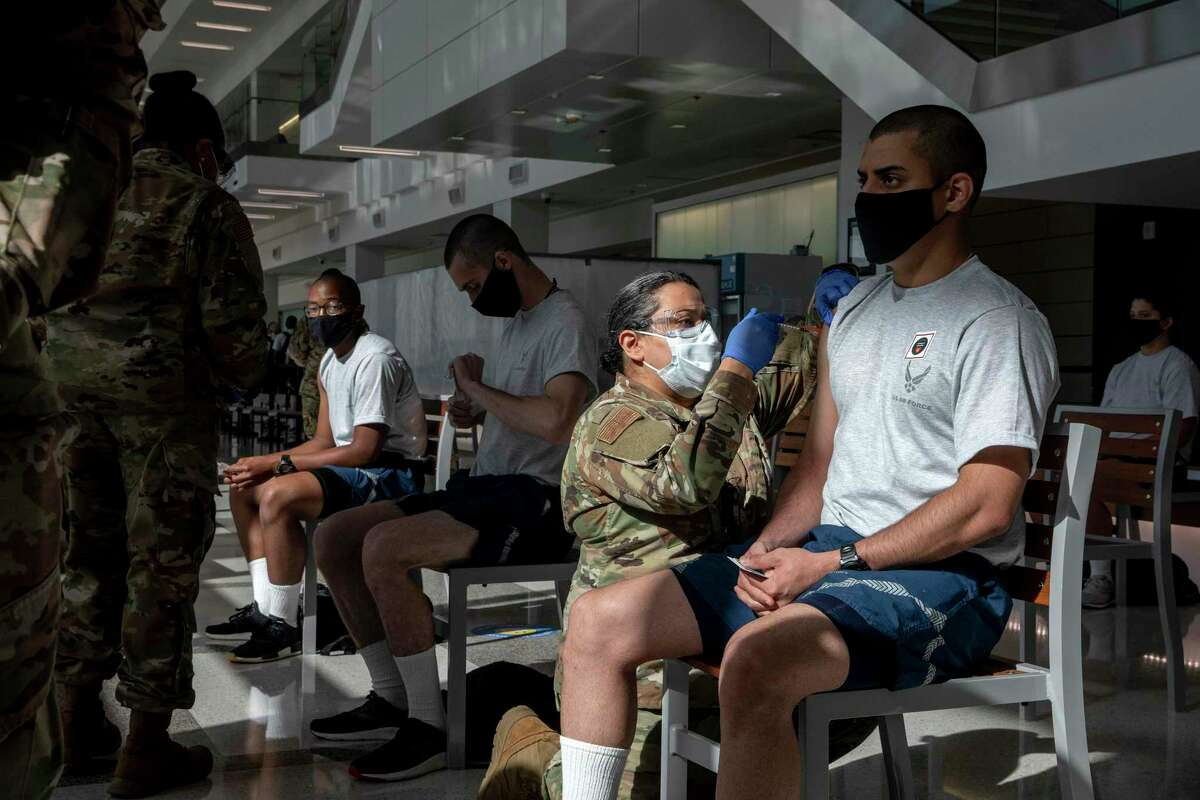 Air Force recruits get vaccinated at Lackland Air Force Base. Policies about masks aren't in alignment for military school districts, a problem for students but also military readiness.