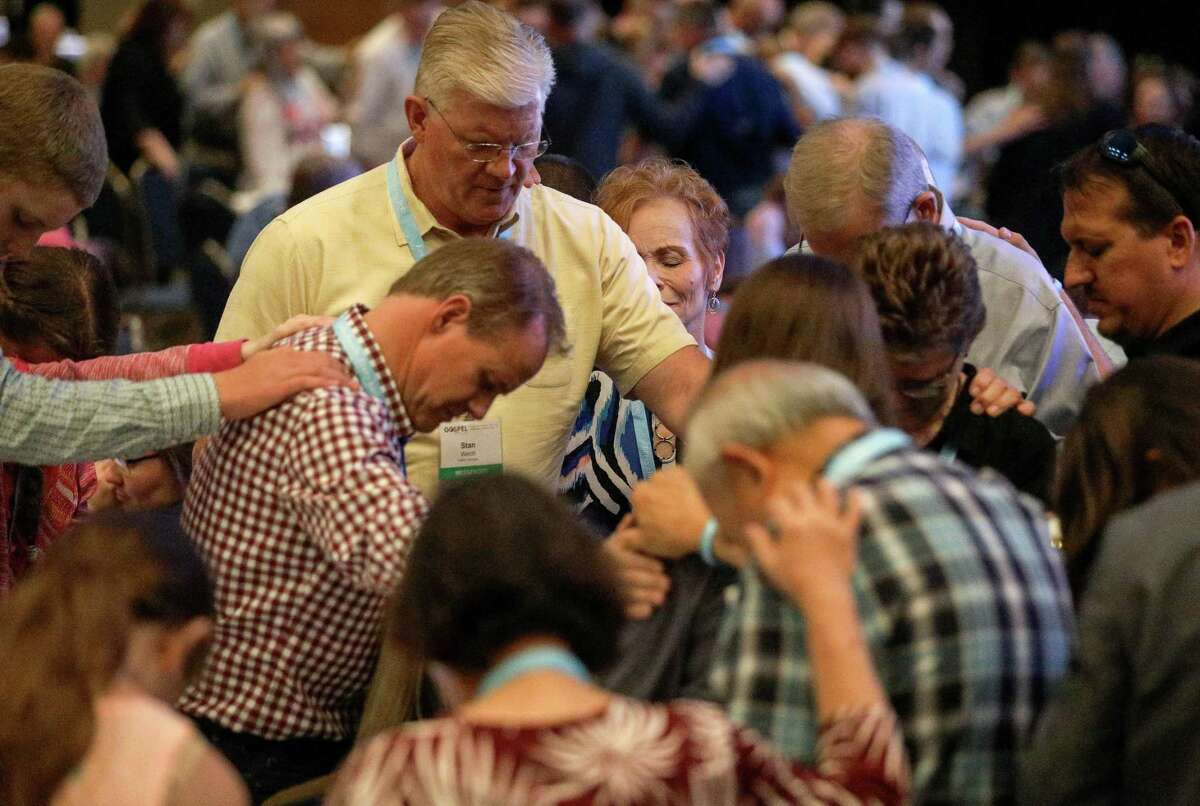 Melody Welch, center, and her husband Stan Welch, left, pray at the International Mission Board dinner on the eve of the the Southern Baptist Convention's annual meeting on June 10, 2019, in Birmingham.