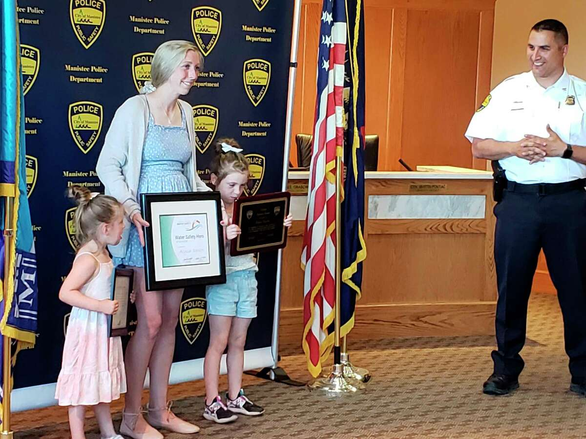 Alyssa Dewitt stands with daughters Cleo Knapp (left) and Briar Knapp after Manistee City Police Chief Josh Glass (right) presented her with several awards.Dewitt saved several children from a near drowning incident at First Street Beach last month. (Arielle Breen/News Advocate)