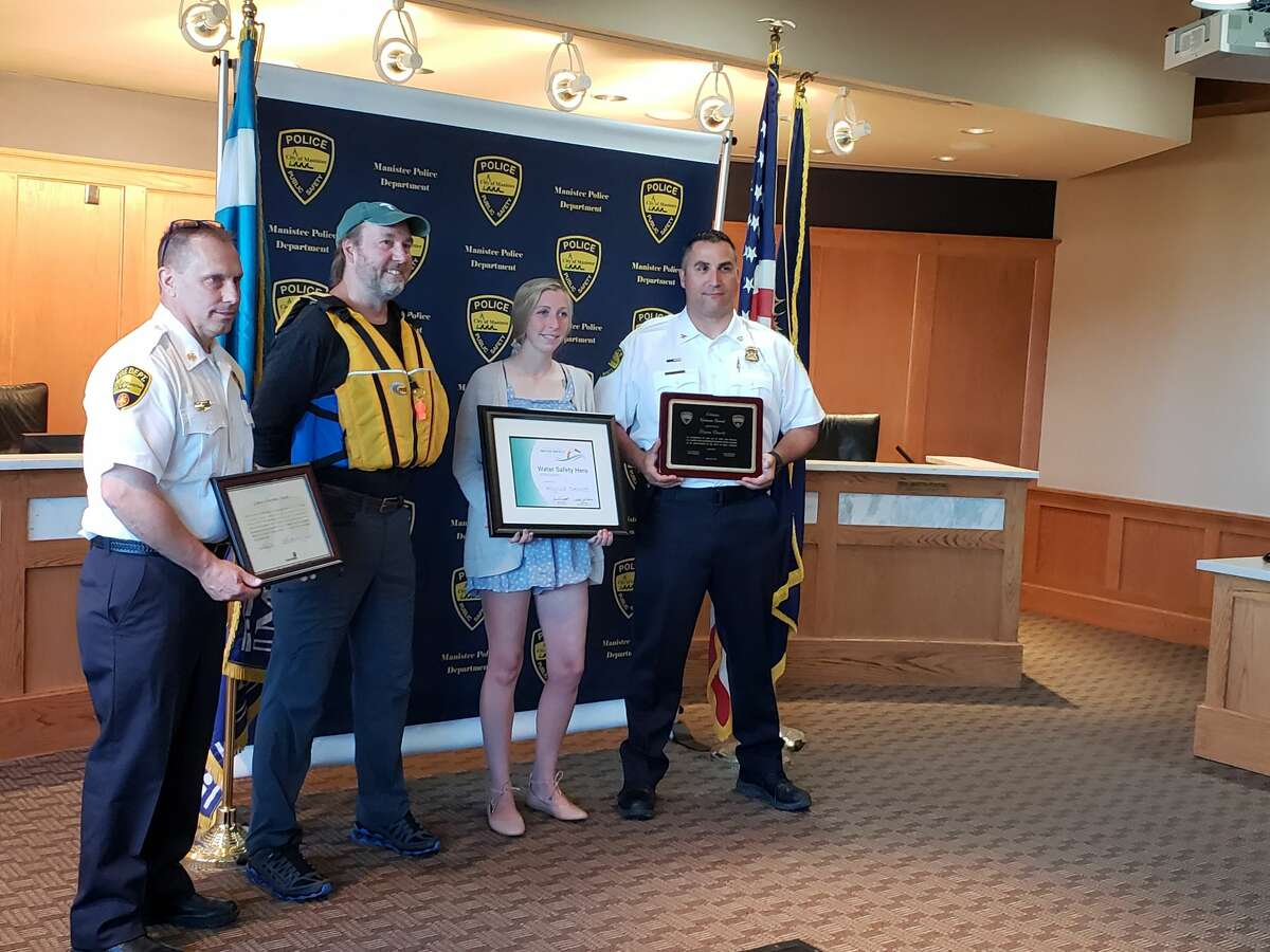 Mark Cameron, Jamie Racklyeft, Alyssa Dewitt aand Josh Glass are shown after an award ceremony for Dewitt for her efforts in saving three children from drowning at First Street Beach, in Manistee on May 25.