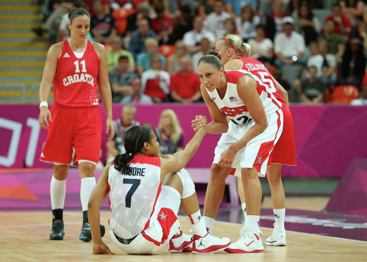 Diana Taurasi #12 of United States helps up teammate Maya Moore #7 of United States after she was knocked down by Andja Jelavic #5 of Croatia during Women's Basketball on Day 1 of the London 2012 Olympic Games at the Basketball Arena on July 28, 2012 in London, England.
