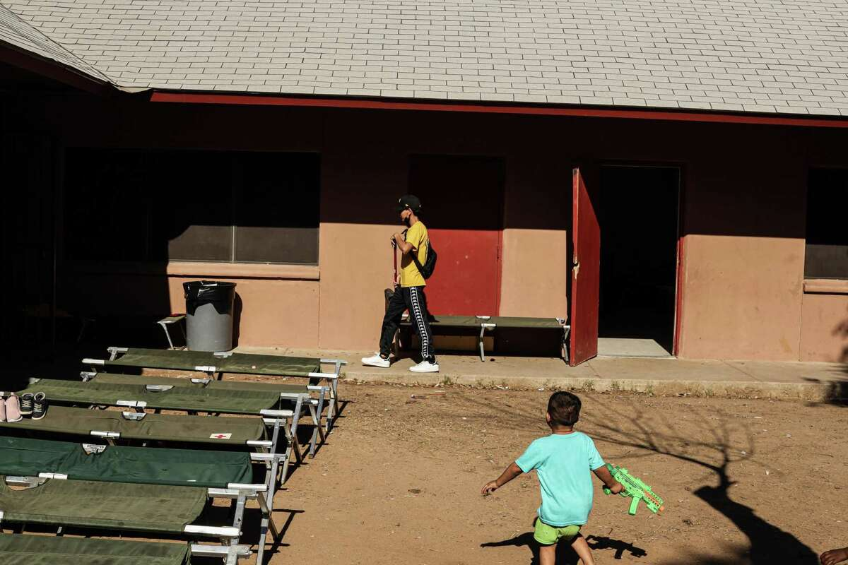 A migrant child plays in a courtyard at the Holding Institute shelter in Laredo last month. Gov. Greg Abbott's recent order is particularly cruel.