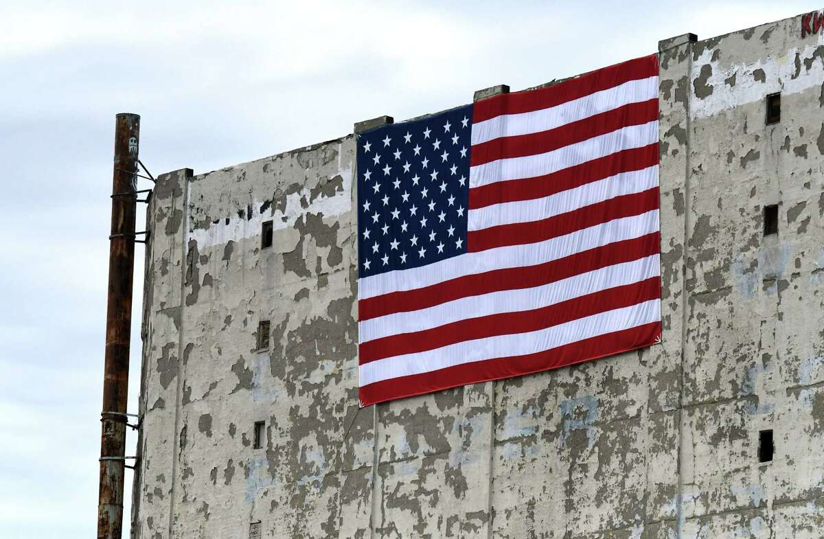A large U.S. flag was recently hung atop Central Warehouse on Friday, June 11, 2021, in Albany, N.Y. The City of Albany is accepting bids for the former cold storage facility. (Will Waldron/Times Union)