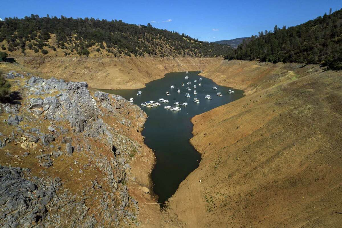 Houseboats whose owners chose to leave them in the lake, float at a water level nearly 200 feet below normal at the Lime Saddle Marina for Lake Oroville near Paradise, Calif. The punishing drought conditions afflicting most of California are expected to endure for months, climate experts with the National Oceanic and Atmospheric Association said Thursday.
