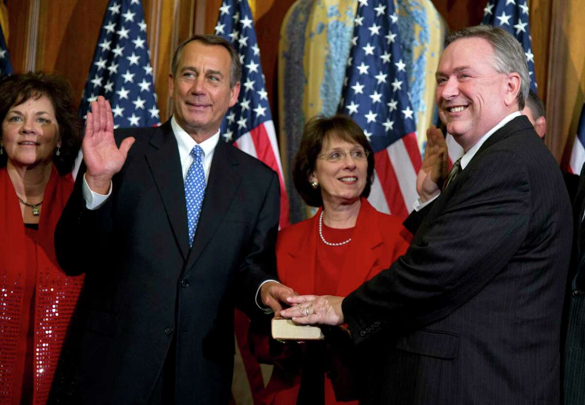 FILE - In this Jan. 3, 2013, file photo, Rep. Steve Stockman, R-Texas, right, participates in a mock swearing-in ceremony with Speaker of the House Rep. John Boehner, R-Ohio, for the 113th Congress in Washington. Stockman, a suburban Houston Republican is mounting a long-shot challenge from the right against Senate minority whip John Cornyn but has made virtually no public appearances in Texas as questions mount about his campaign finances. Now, he's stopped showing up for his day job, too. (AP Photo/ Evan Vucci, File)