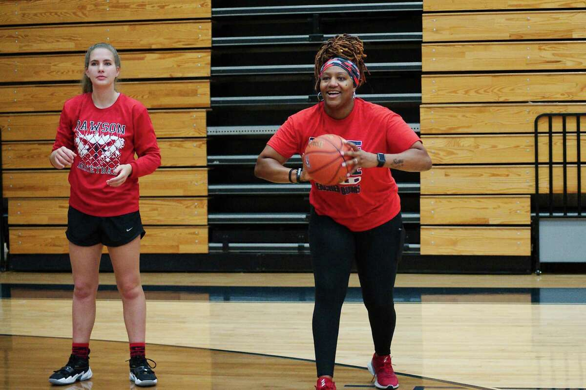Dawson basketball player Sarah Allison (left) and Dawson first-year head coach Sharee Griffin work with players during a drill at the Dawson summer girls' basketball camp.