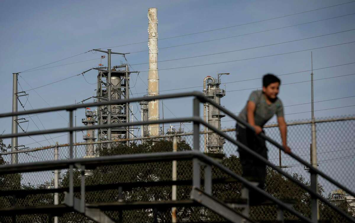 The Valero Houston Refinery is seen in the background as a child climbs on bleachers Wednesday, Jan. 27, 2021, at Hartman Park in Houston.