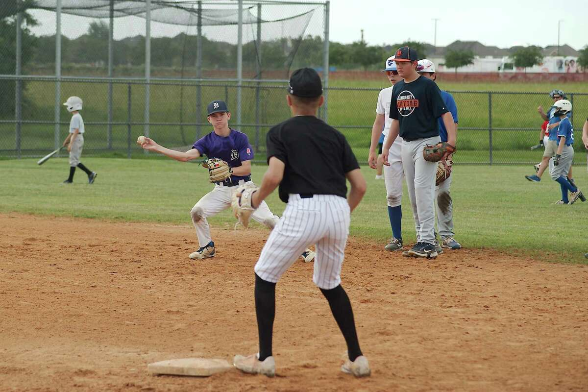 Drew Floyd throws to Nathan Patel during a fielding and throwing drill at the Clear Springs summer baseball camp.