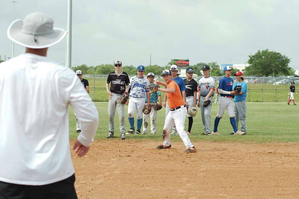 Evan Swartz participates in a fielding and throwing drill while Clear Springs baseball coach Chris Floyd observes at the Clear Springs summer baseball camp.