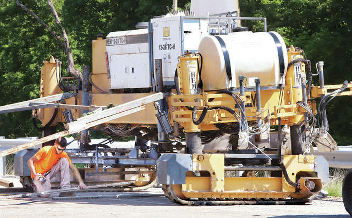 An employee of Baxmeyer Construction Inc., from Waterloo, does some maintenance work Friday on one of the company's concrete paving machines in New Delhi, in Jersey County. Concrete pavement work is set to resume Monday from just south of Delhi Road to Stagecoach Road as part of the $18.6 million, 2.4-mile project expanding U.S. 67 to four-lanes in that area. The project is expected to be completed by late 2022.