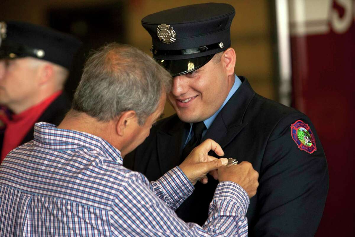 Giovanni Valentini pins a badge onto his son John during a Greenwich Fire Department swearing-in ceremony at its headquarters in Greenwich, Conn., on Friday June 11, 2021. COVID-19 postponed the earlier swearing-in ceremony for three firefighters.