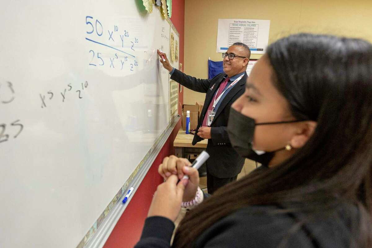 Southside ISD Superintendent Rolando Ramirez races against high school student Adylissa Gomez during a friendly competition to solve a math problem last June during a classroom visit.