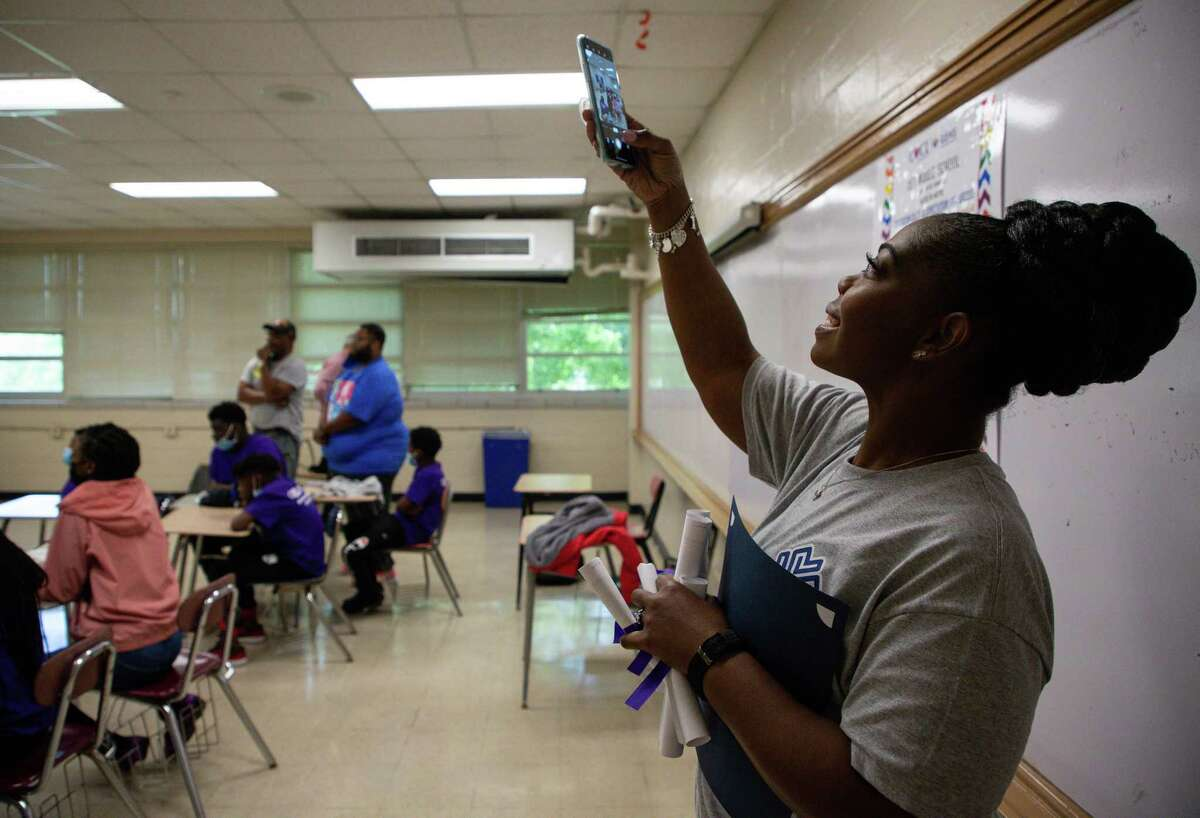 Gaining Empowerment in Middle Schools manager Brandi Walker-Brown takes a photo as her students interact with Derek Dominique, an artist, producer and songwriter invited to speak to the class during the last session of the school year.