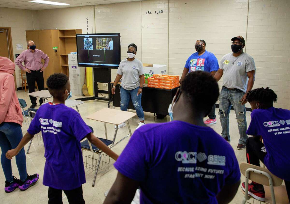 GEMS manager Brandi Walker, center, asks her students what they took away from being in the program this school year, during their last session before summer school at Key Middle School on Tuesday, June 8, 2021, in Houston. GEMS - Gaining Empowerment in Middle School - focuses on the social, emotional and brain developmental needs of middle school students of incarcerated parents.