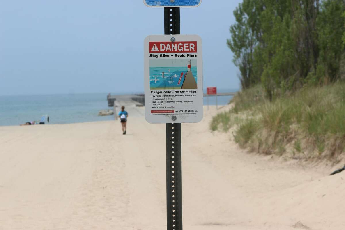 A sign at Manistee's First Street Beach warns visitors to avoid swimming near piers.
