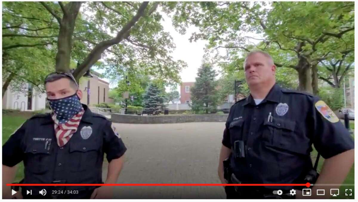 Danbury Police Chief Patrick Ridenhour announced an internal investigation into an incident he filmed at the Danbury Public Library. A screenshot from the video shows two of the officers who responded after a YouTuber filmed inside the library.