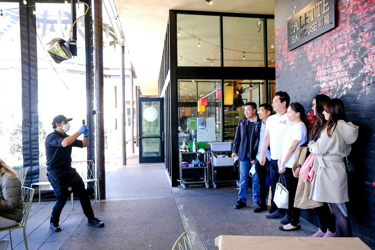 Bar manager Carlos Hernandez takes a photo for a group of diners after their meal at Palette Tea House in San Francisco.