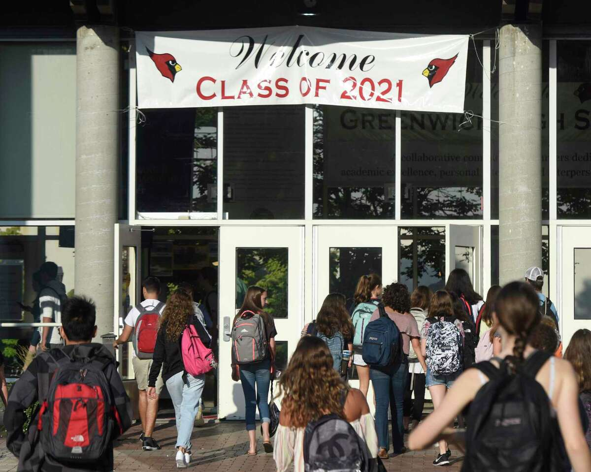 Students walk into school on the first day of the 2017-18 school year at Greenwich High School on Aug. 31, 2017. The banner above the doors welcomes the Class of 2021.