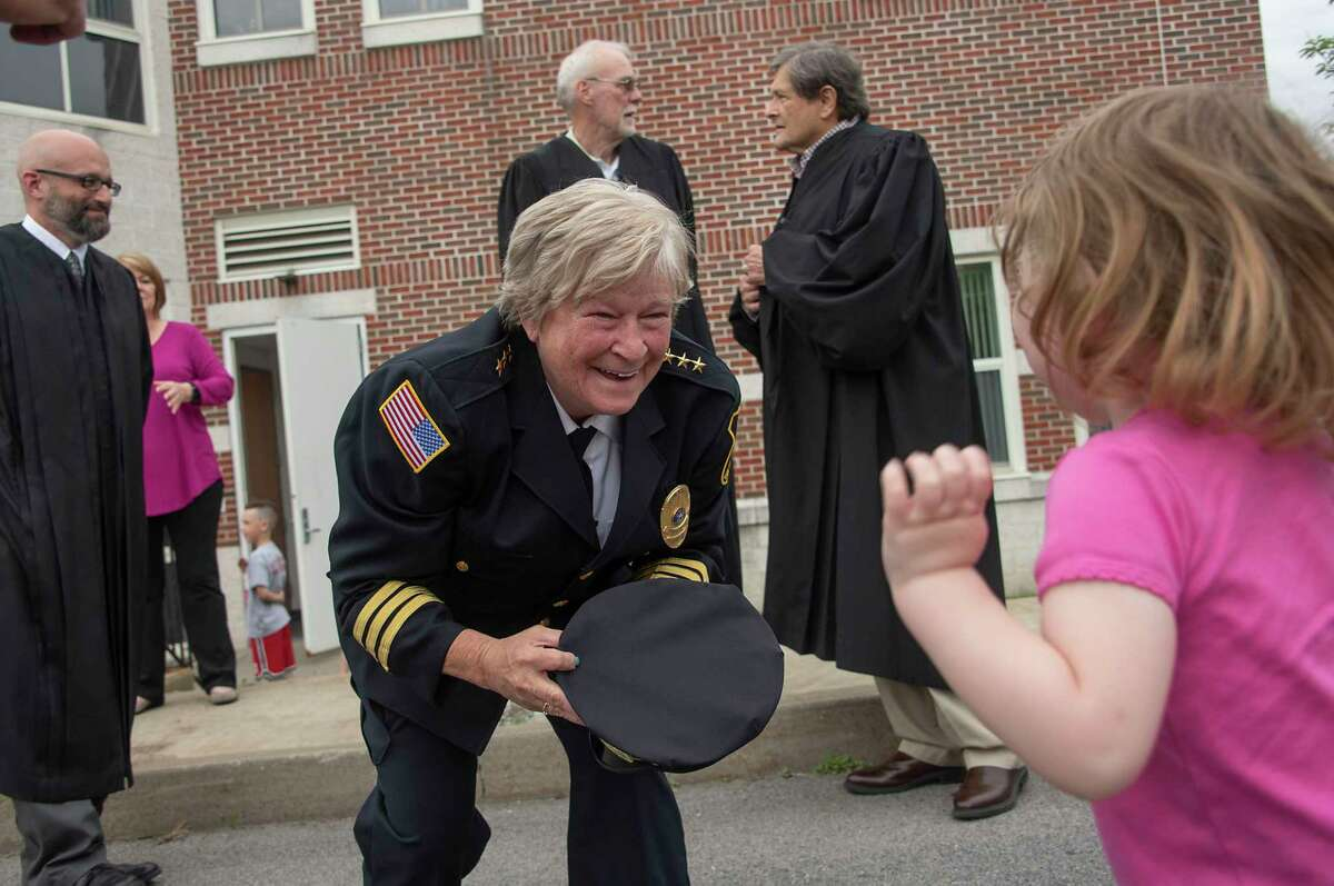Outgoing Police Chief Frances Wall smiles at Taylor Kim, 2, before putting her chief hat on her as the Niskayuna Police Department honored her with a walk out ceremony outside the police department on Friday, June 11, 2021 in Niskayuna, N.Y. (Lori Van Buren/Times Union)