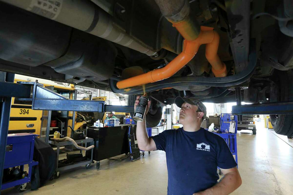 SAISD Mechanic Armando Cortez spray paints a section of the fleet vehicle's emission system, notably the catalytic converters as part of an effort to deter would-be catalytic converter thieves on Friday, June 11, 2021.