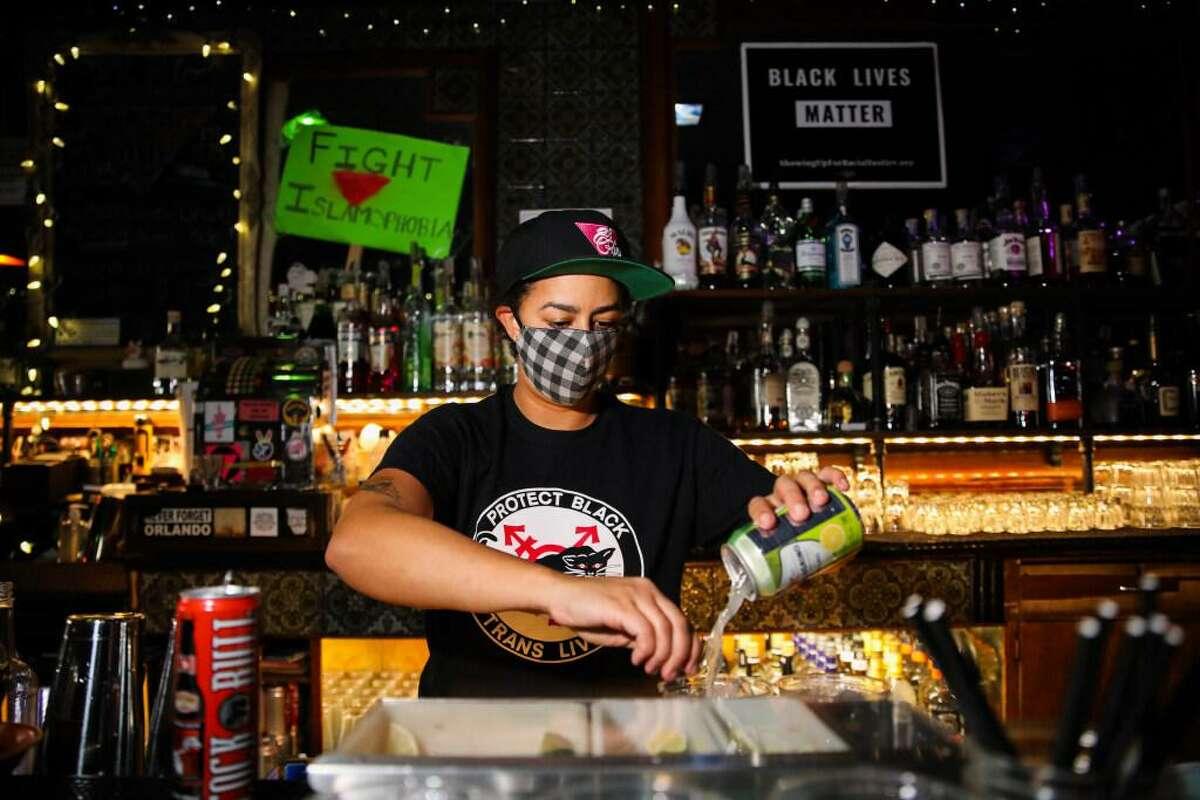 Bartender Jasmine Johnson makes drinks at El Rio in San Francisco in April.