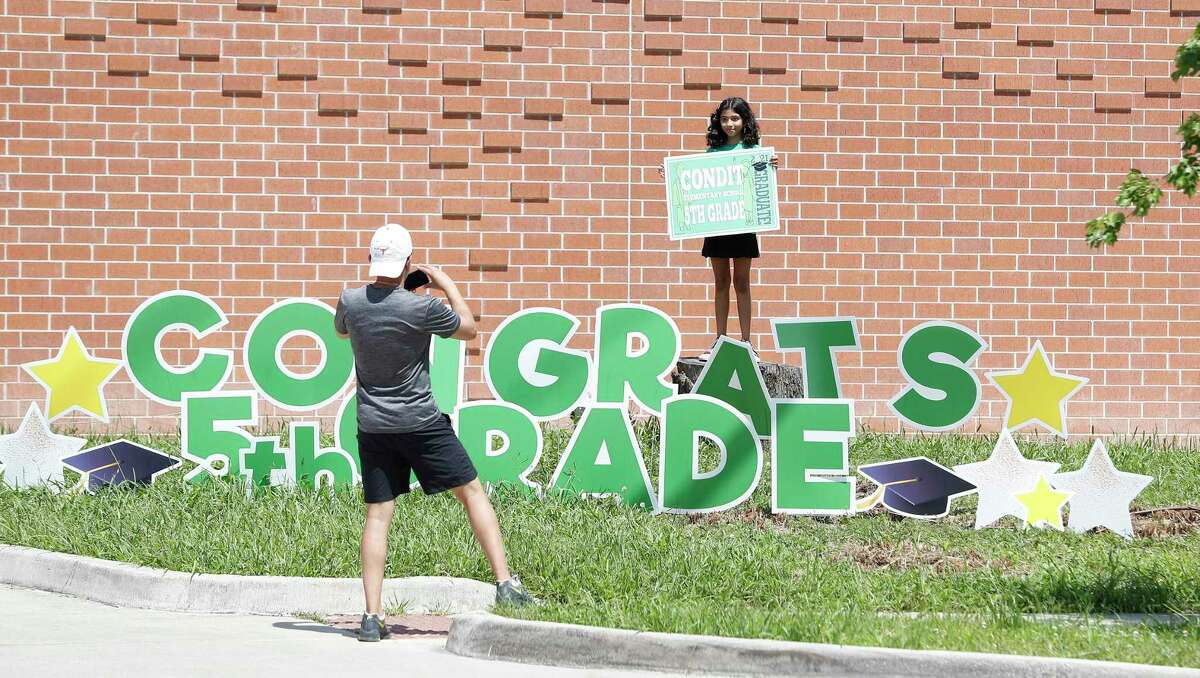 Shreyas Bhavsar takes a photo of his fifth-grade daughter, Maya, on the last day of the 2020-21 school year Friday outside Houston ISD's Condit Elementary School.