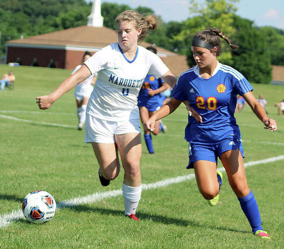 Marquette's Haley Williams (8) and Roxana's Reagan Lynn chase the ball during Friday's Class 1A sectional championship game at the Wood river Soccer Park.
