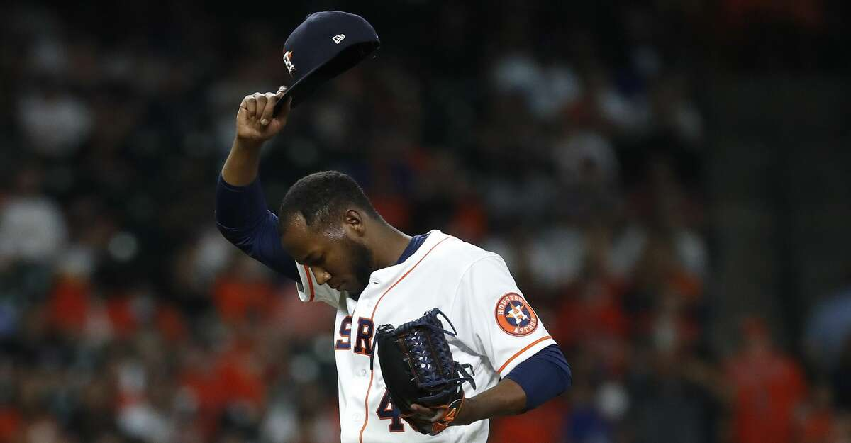 Houston Astros relief pitcher Enoli Paredes (48) wipes his face during the eighth inning of an MLB baseball game at Minute Maid Park, Tuesday, May 25, 2021, in Houston.