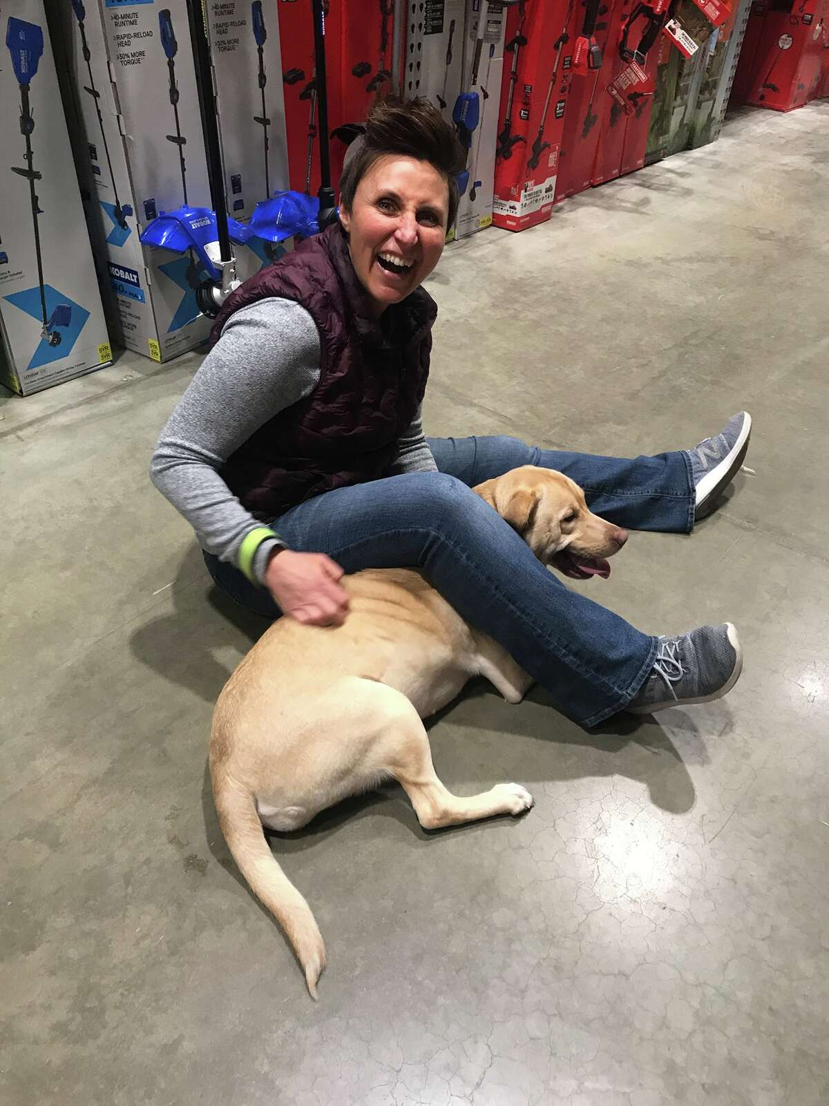 Trainer Joni Bonilla frolics with a dog before a service training session at Operation At Ease in Rotterdam.