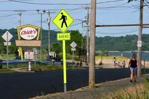 People walking along the beach pass a vacant Chick's Drive-In on Beach Street in West Haven on June 11, 2021.