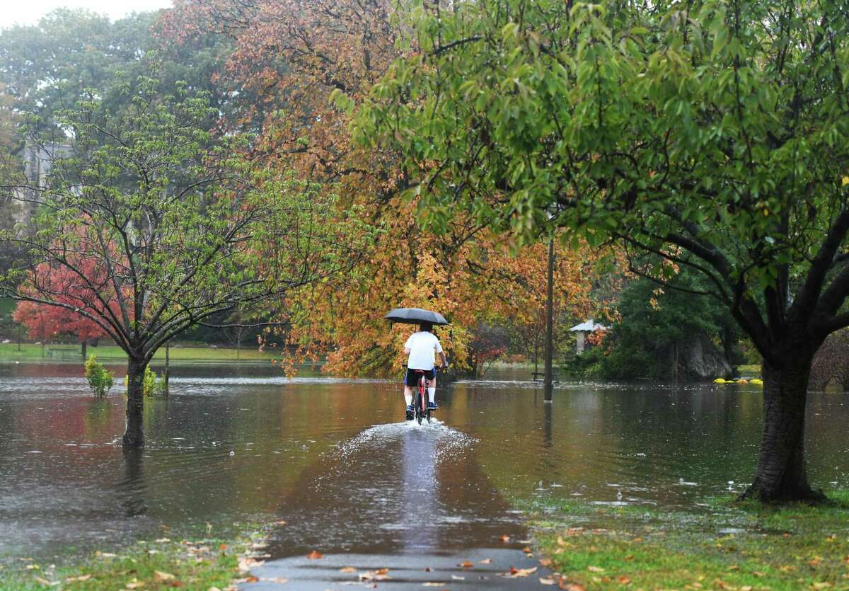 Old Greenwich resident Reed Kemp, 15, rides his bike along a heavily flooded path as rain continues to fall at Binney Park in Old Greenwich, Conn. Sunday, Oct. 27, 2019. Areas of Old Greenwich, Cos Cob and Byram could be vulnerable to future storms due to rising sea levels, according to an ongoing study of Greenwich's coastal resiliency.