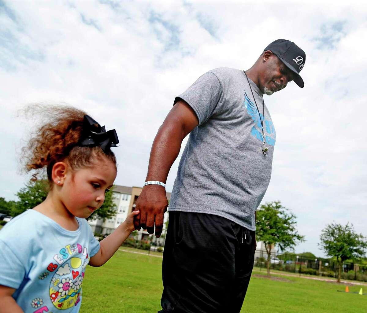 Coach Dominic Cameron helps Zoe Vela,4, go for her water break. For the past 10 years, physical education teacher Dominic Cameron has hosted DC Speed Camp, a free 16-week program for youth and teens to work on athletic and agility skills at IDEA Harvey E. Najim charter school, on Sunday, June 6, 2021.