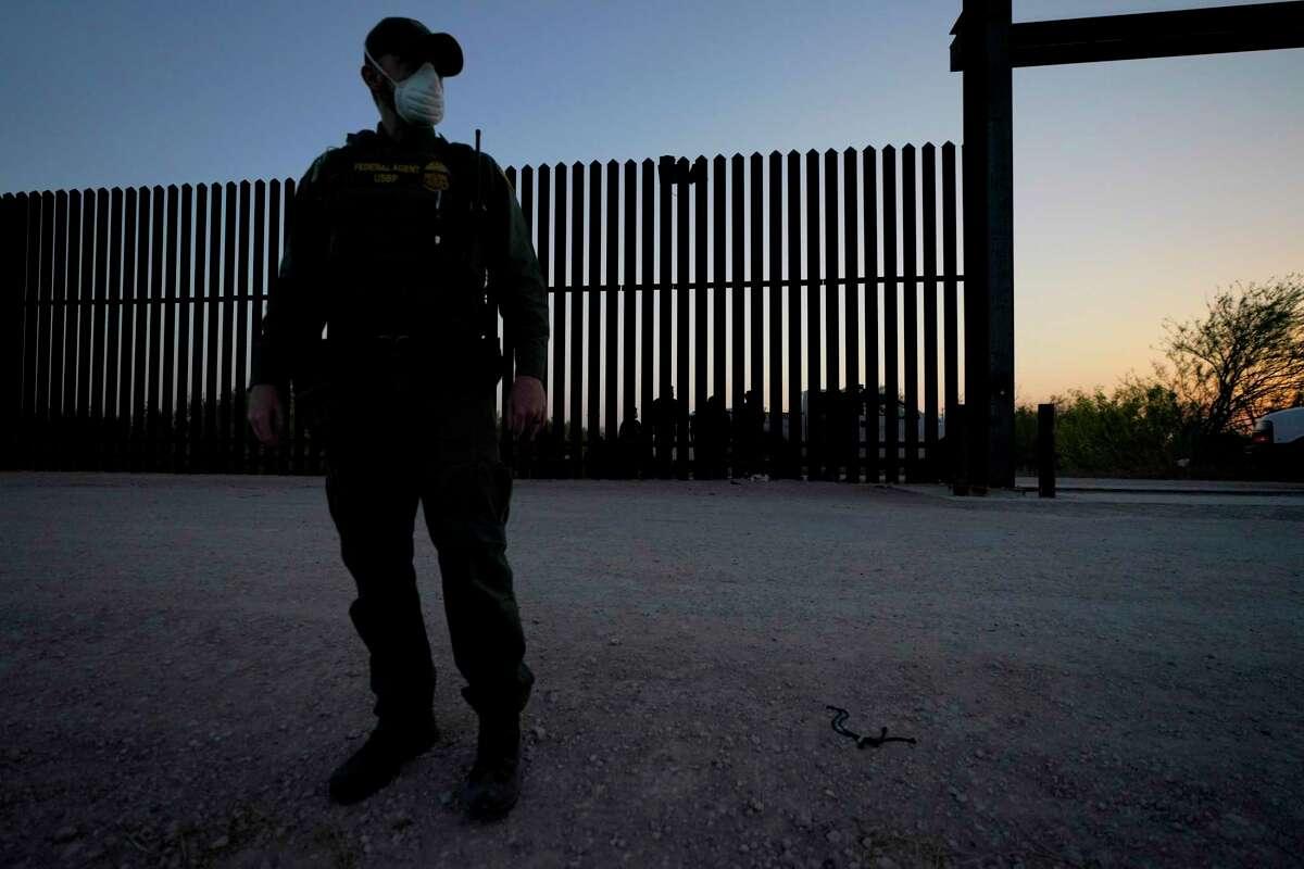En esta fotografía de archivo del 21 de marzo de 2021, un agente de la Oficina de Aduanas y Protección Fronteriza monta guardia cerca de una puerta en el muro en la frontera entre México y Estados Unidos durante un operativo de detención de migrantes, en Abram-Perezville, Texas.