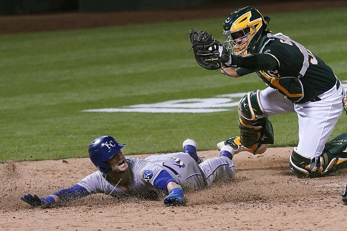 Kansas City Royals' Andrew Benintendi, left, looks for the call after being tagged out at home by Oakland Athletics catcher Aramis Garcia during the eighth inning of a baseball game in Oakland, Calif., Friday, June 11, 2021. (AP Photo/Jeff Chiu)