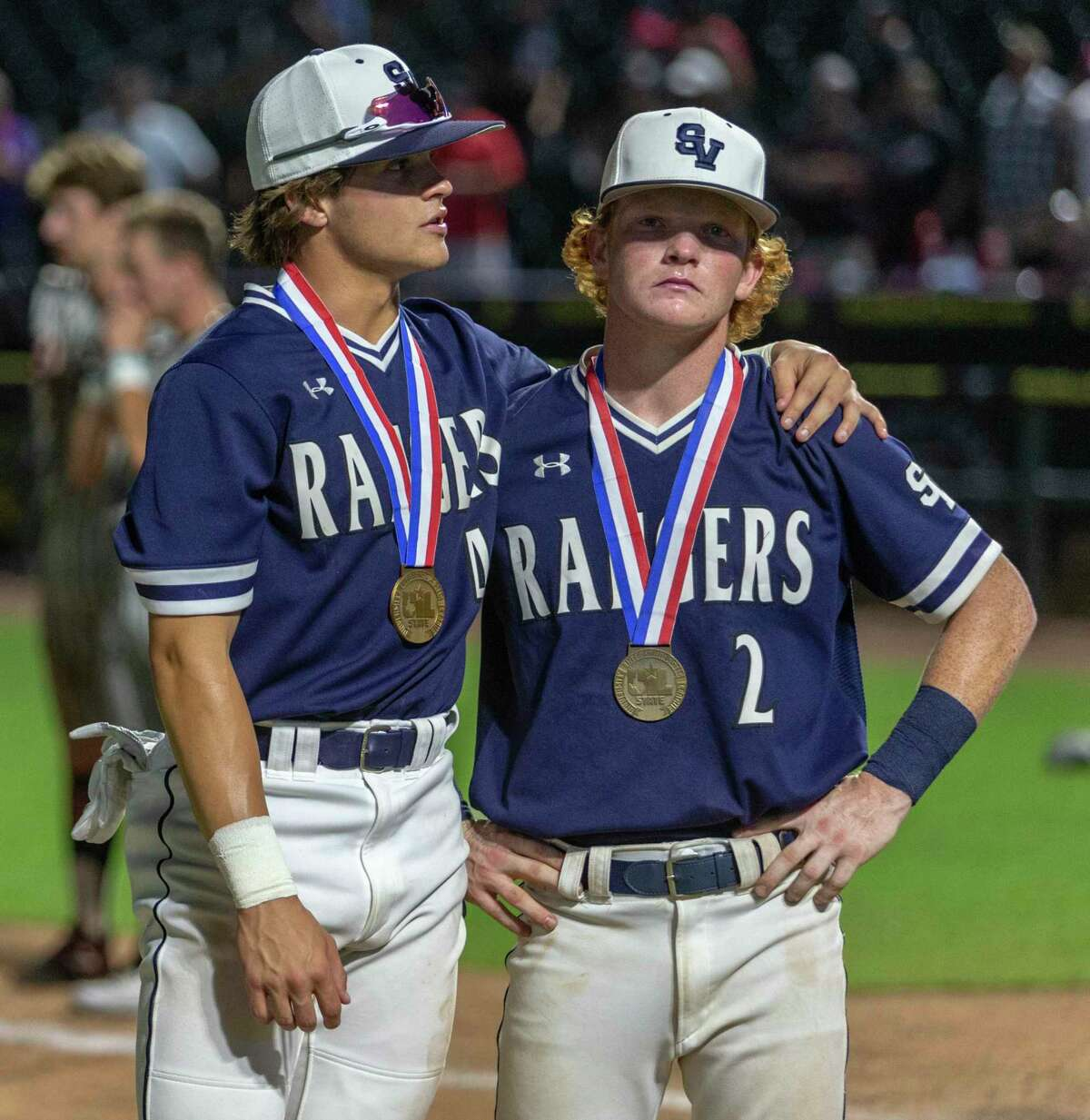 Smithson Valley baseball players Kasen Wells, left, and Ryan Ruff wear their UIL state semi-finalist medals Friday night, June 11, 2021 at the Dell Diamond in Round Rock after the Rangers lost to Rockwall-Heath.