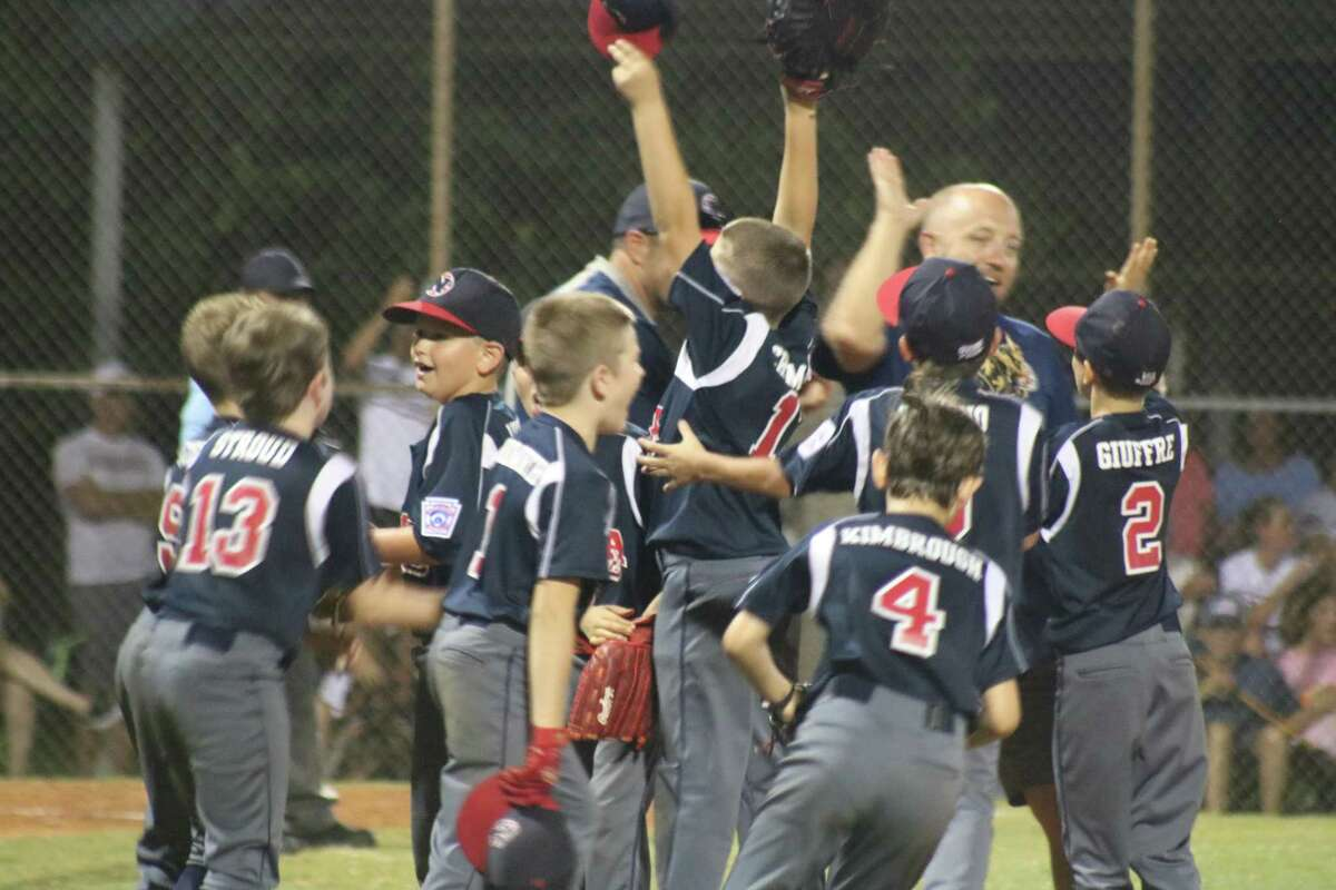 The NASA Area Little League 9-year-old all-stars celebrate with their coaches after winning the District 14 crown Friday night at Rudy Trabanino Field.